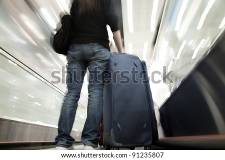 Traveler with a bag at the  escalator - stock photo
