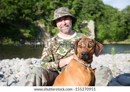 Traveler with a Rhodesian Ridgeback by the river. - stock photo