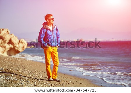 traveler with backpack standing on the beach against the sea and blue sky at early morning