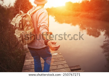 traveler with backpack walking over wooden bridge on the lake in sunset - stock photo