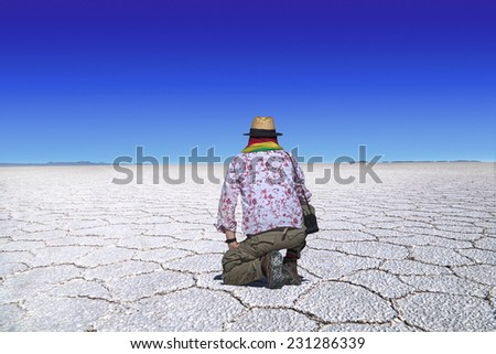 Traveler with straw hat and scarf in bolivian national colors kneels at the desert of Uyuni, Bolivia and looks at the wideness of the desert. - stock photo