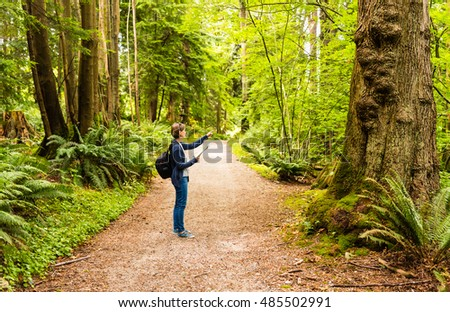Traveler woman finding her way in green forest and showing direction. Stanley park Vancouver Canada