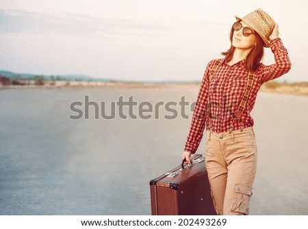 Traveler woman in hat and sunglasses with vintage suitcase, hipster style. With light effects - stock photo