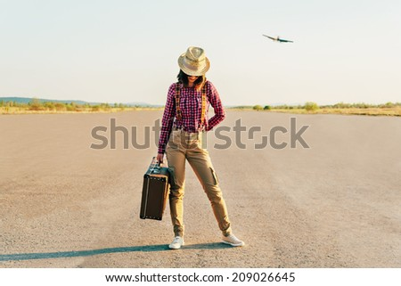 Traveler woman in hat stands on road with vintage suitcase. Hipster style woman
