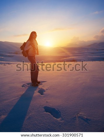 Traveler woman in the high snowy mountains enjoying beautiful sunset, active winter holidays, healthy and sportive lifestyle - stock photo