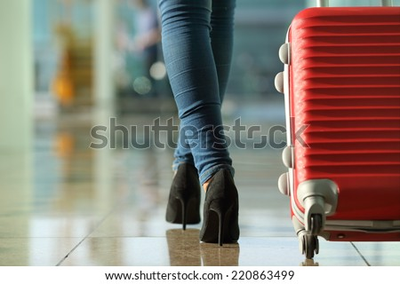 Traveler woman legs walking carrying a suitcase in an airport - stock photo