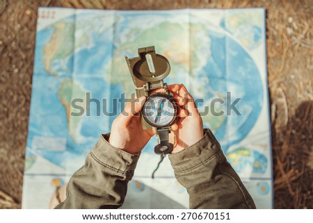 Traveler woman searching direction with a compass on background of map outdoor. Close-up. Point of view shot - stock photo
