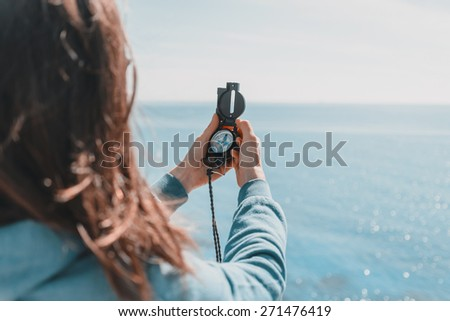 Traveler woman searching direction with a compass on coastline near the sea in summer - stock photo