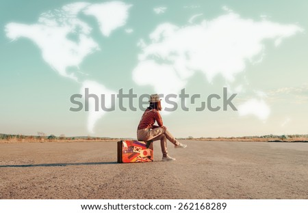 Traveler woman sitting on a suitcase and dreaming about adventures. Map of the world is painted in sky. Concept of travel - stock photo