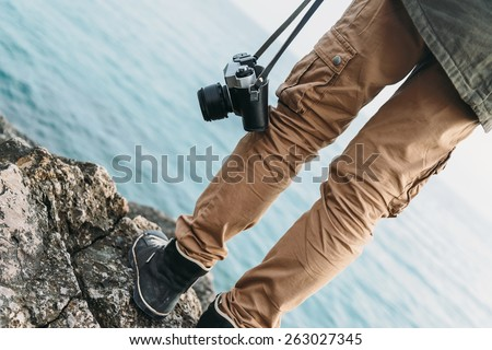Traveler woman with old photo camera standing on stone coast near the sea. View of legs - stock photo