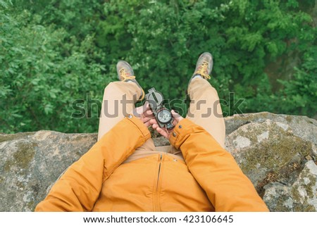 Traveler young man sitting on edge of cliff and searching direction with a compass in summer outdoor. Point of view shot - stock photo