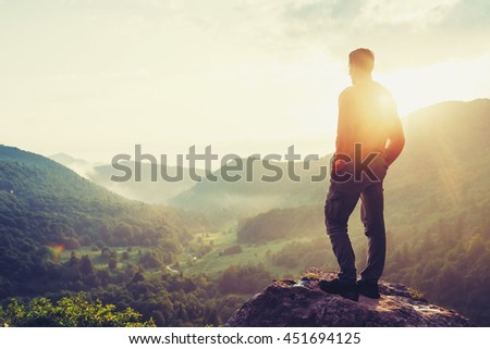 Traveler young man standing in the summer mountains at sunset and enjoying view of nature. Image with instagram color