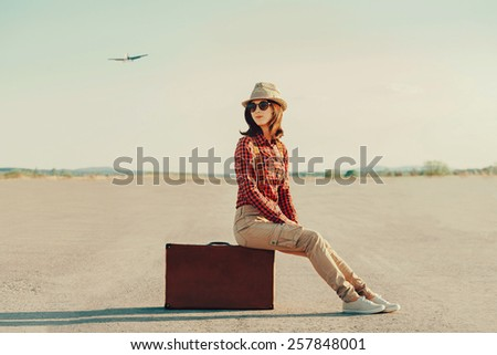 Traveler young woman in a hat sitting on suitcase on road. Airplane flying in the sky - stock photo