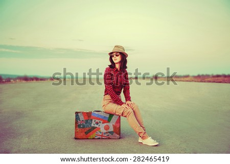 Traveler young woman sitting on a suitcase on road outdoor. Suitcase with stamps flags representing each country traveled - stock photo