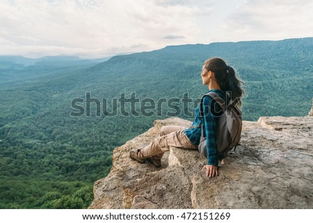 Traveler young woman sitting on edge of cliff and looking on mountains in summer