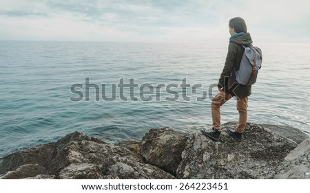 Traveler young woman standing on stone on coast and enjoying view of sea - stock photo