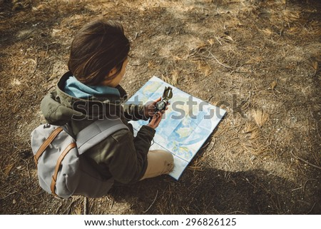 Traveler young woman with backpack searching direction with a compass on background of map in the forest. Focus on compass - stock photo