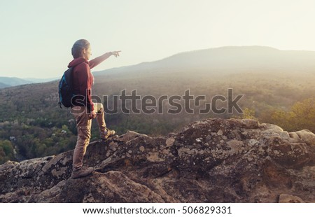 Traveler young woman with backpack standing on top of rock and pointing at mountains in autumn