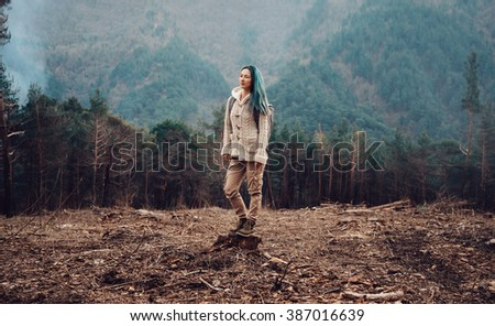 Traveler young woman with backpack standing on tree stump in the forest outdoor - stock photo