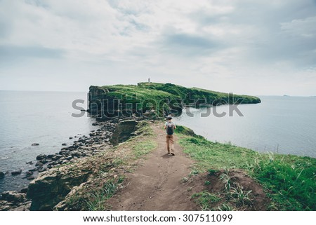 Traveler young woman with backpack walking on island in the sea in summer, rear view