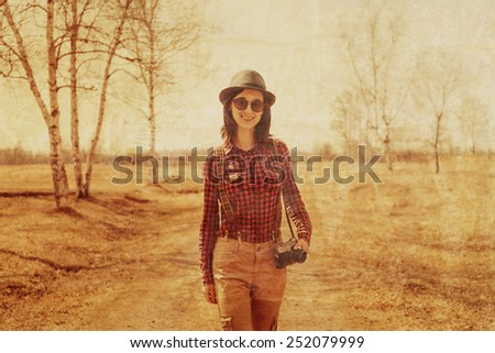 Traveler young woman with old photo camera on path outdoor. Image with vintage filter - stock photo