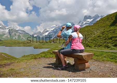 Travelers at a mountain lake. Switzerland - stock photo