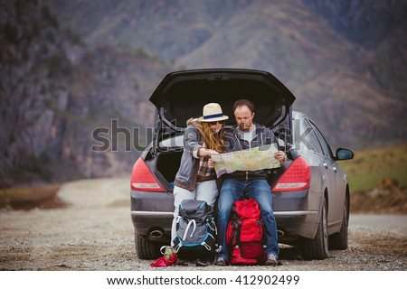 Travelers by car in the mountains in spring see the map