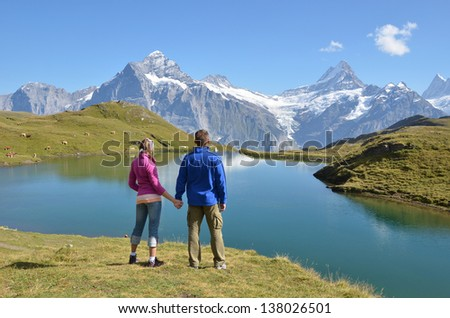 Travelers enjoying Alpine panorama. Jungfrau region, Switzerland - stock photo