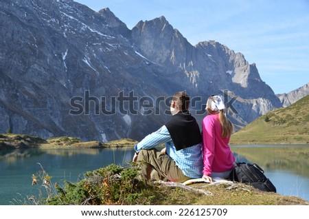 Travelers enjoying alpine view. Switzerland - stock photo