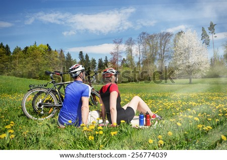 Travelers having rest in Alpine meadow - stock photo