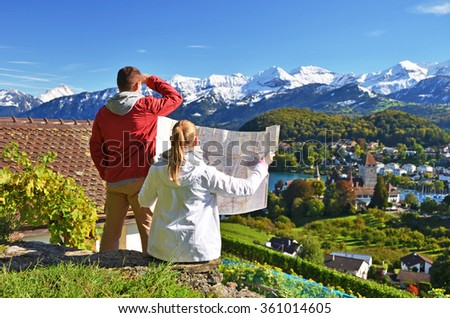 Travelers looking to the mountains. Switzerland - stock photo