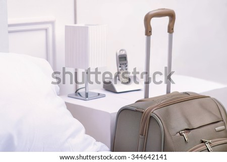 Travelers necessity. Big packed travelers suitcase is standing beside the bed table in hotel room - stock photo