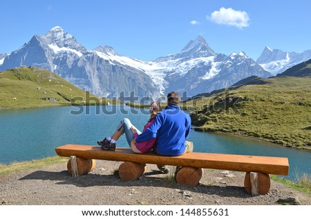 Travelers on a bench enjoying Alpine panorama. Jungfrau region, Switzerland - stock photo