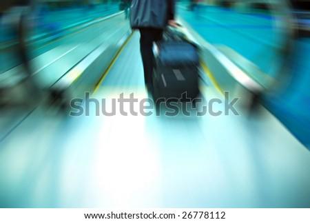 Travelers rushing through an airport terminal - stock photo