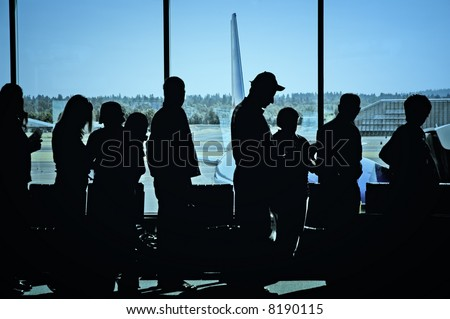 Travelers standing in line at the airport waiting to board an airplane