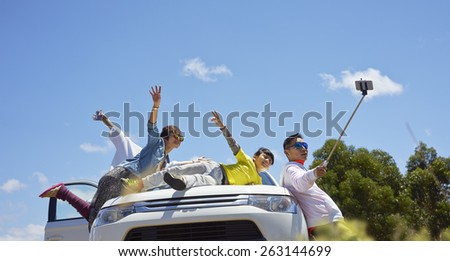 travelers taking photos with selfie stick - stock photo