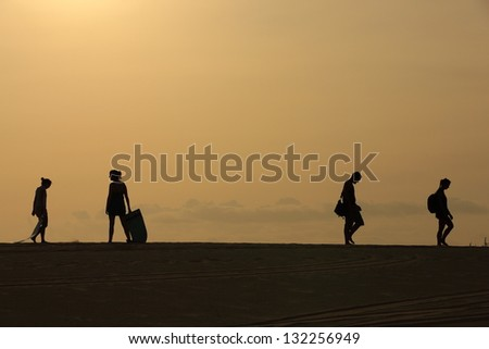 Travelers walking on white sand dunes