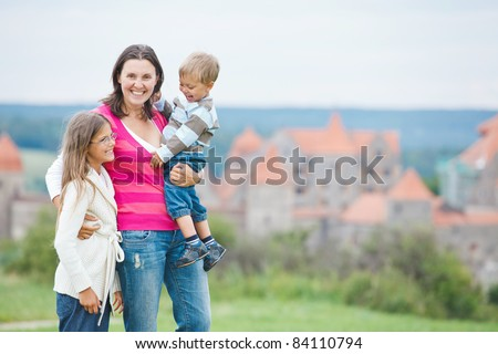 Travelers. Young mother with her two children on a tour of European medieval castles. - stock photo