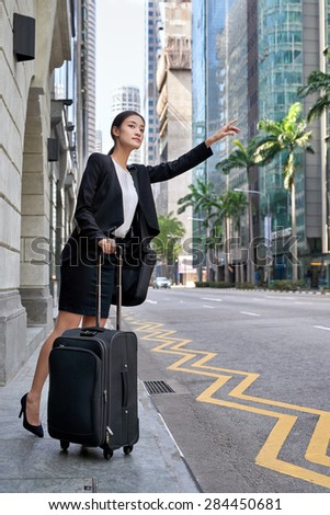 traveling asian chinese business woman calling for taxi cab from city street sidewalk - stock photo