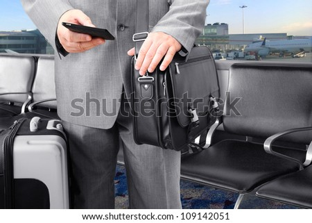 Traveling Businessman Calling by Phone at the airport - stock photo