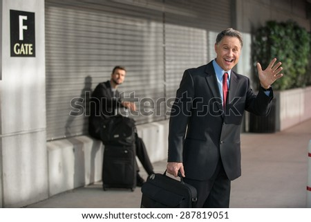 Traveling businessman with smile after arriving at the airport - stock photo