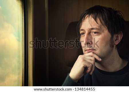 Traveling by train. Man traveling by train, looking through the dirty window. - stock photo