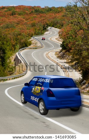 traveling car in flag of us state of wisconsin colors and beautiful road landscape for tourism and touristic adertising - stock photo