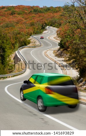traveling car in national flag of jamaica colors and beautiful road landscape for tourism and touristic adertising - stock photo