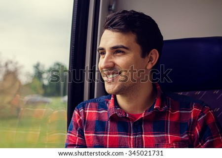 Traveling Comfort -Young man smiling feeling relaxed traveling by train.Young man traveling looking out the window while sitting in the train. - stock photo