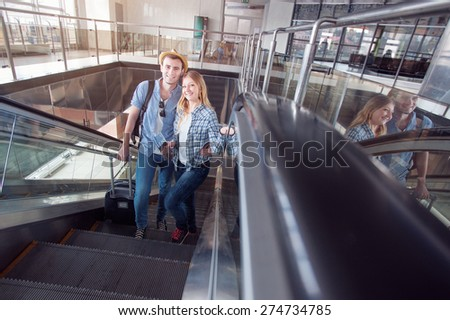 Traveling concept. Happy loving couple in casual wear on an escalator of the airport terminal. - stock photo