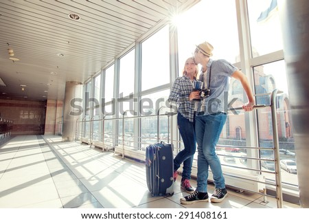 Traveling concept. Waiting for boarding. Happy loving couple in casual wear standing in airport terminal holding passport with tickets. - stock photo