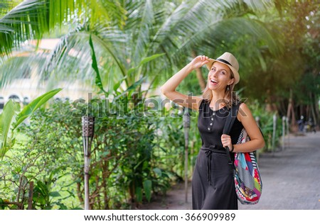 Traveling concept. Young smiling woman with hat and backpack walking by tropical park.