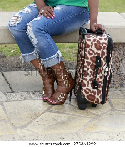 Traveling contest: beautiful legs of African-American woman in ragged jeans with suitcase - stock photo