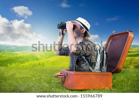 Traveling explorer observes nature from a luggage - stock photo